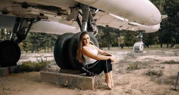美しい若いブルネットの少女は、古い軍用機の背景に立っています。自然の中で白いシャツと黒いズボンの女の子。軍事機器。ポートレートハーフレングス。ポーズをとる女の子