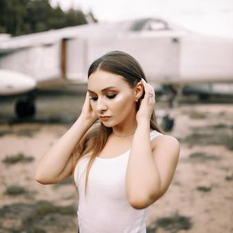 美しい若いブルネットの少女は、古い軍用機の背景に立っています。