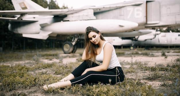 아름 다운 젊은 갈색 머리 소녀는 오래 된 군용 항공기의 공간에 서