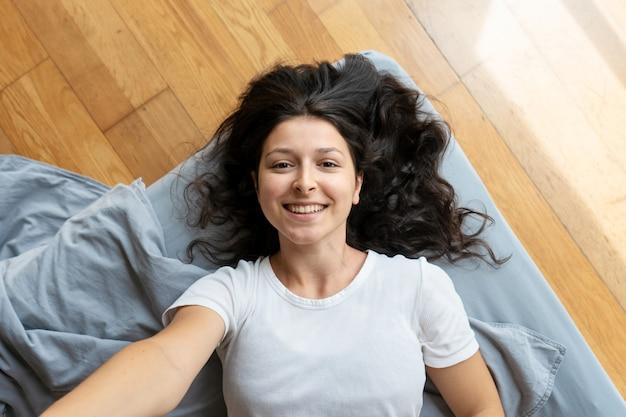 Красивая молодая брюнетка девушка принимает селф. вид сверху. хорошее настроение