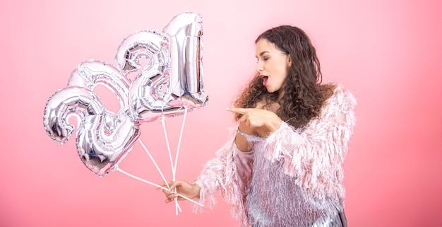 Bella giovane ragazza castana con capelli ricci vestita a festa emotivamente in posa su uno sfondo rosa con luce calda con palloncini d'argento per il concetto di nuovo anno