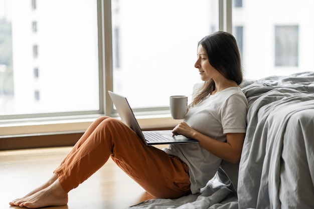 Beautiful young brunette girl working on a laptop and drinking coffee, sitting on the floor near the bed by the panoramic window with a beautiful view from the high floor.  shopping on the internet.