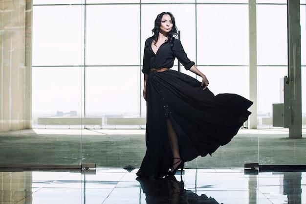 大きなオフィスの窓のそばに黒いドレスを着た美しい若いブルネット