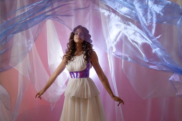 長い白いドレス、軽い空飛ぶ生地、シルクのスカート、素晴らしいきらめきの肖像画の美しい若いブルネット。シュールなスタイル、背景に半透明の生地