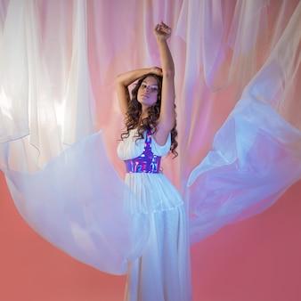 長い白いドレスの光の飛行生地の美しい若いブルネット