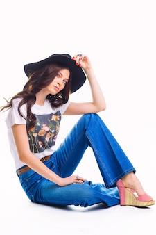 청바지 벨 바닥 흰색 티셔츠와 검은 모자에 아름 다운 젊은 갈색 머리, 바닥에 앉아