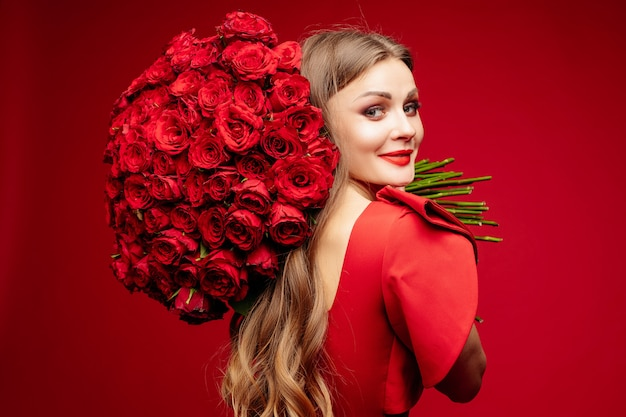 Beautiful young brunette lady in red with bunch of red roses on shoulder