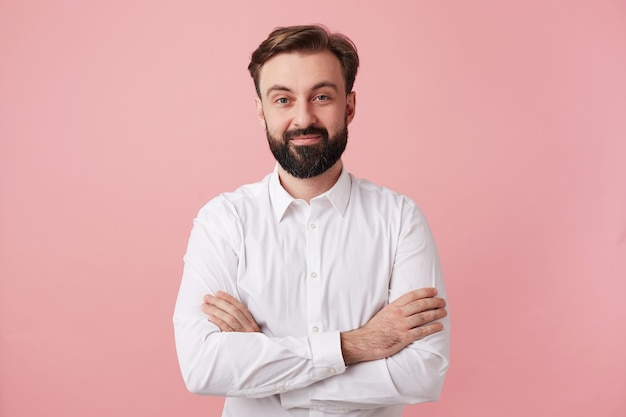 Beautiful young brunette male with beard looking at front with charming positive smile, wearing formal clothes while standing against pink wall with folded hands