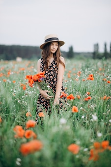 Beautiful young brunette model girl in a hat walks in a flower field with a bouquet of poppies. fragrant field of red flowers.