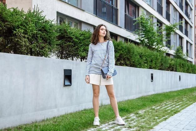 광고를 위해 새로운 컬렉션 옷 카탈로그에서 포즈를 취하는 아름다운 젊은 갈색 머리 모델