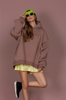 茶色の背景にスポーツウェアネオン靴下キャップとサングラスでポーズをとって美しい若いブルネット
