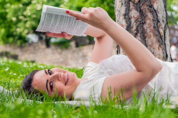 Красивая молодая брюнетка, чтение на лугу в парке