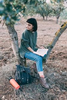 나무 아래 아름 다운 젊은 갈색 머리 앉아 책을 읽고