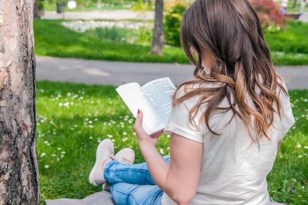 美しい若いブルネットは、公園で新鮮な春に座って、本を読んで。公園で読書している美しい若い女性のクローズアップ。女性、読書、屋外、読書