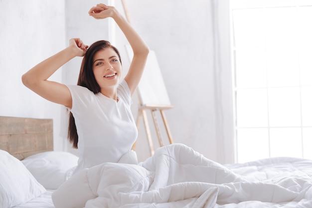 Красивая молодая брюнетка широко улыбается и протягивает руки после восьми часов сна