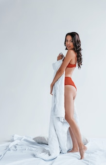 Beautiful young brunette in underwear standing in studio and covering her sexy body by white towel.