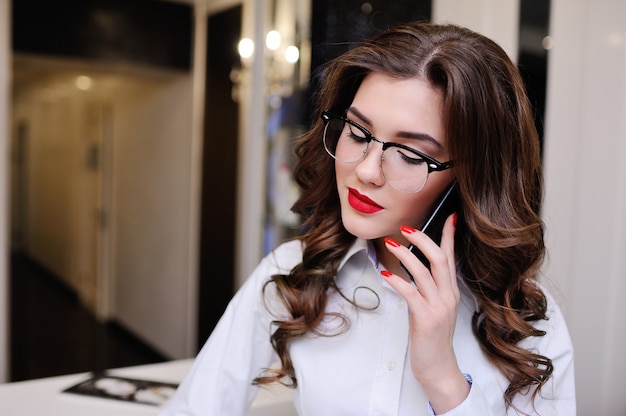 Beautiful young brunette wearing glasses talking on cell phone