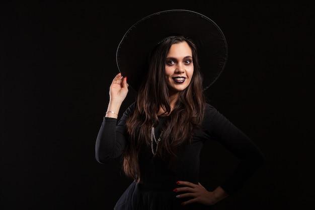 검은 배경 위에 그녀의 손으로 그녀의 모자를 들고 아름 다운 젊은 갈색 머리 마녀. 할로윈을 위해 분장하십시오. 할로윈 마녀처럼 차려입은 예쁜 여자.
