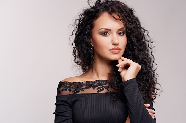 Beautiful young brunette with curly hair and bright makeup