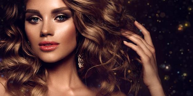 Красивая молодая брюнетка с макияжем и вьющимися волосами