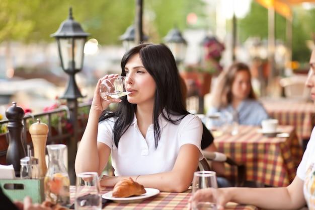 Красивая молодая женщина брюнет в кафе, пьющем белое вино. концепция общения и дружбы.