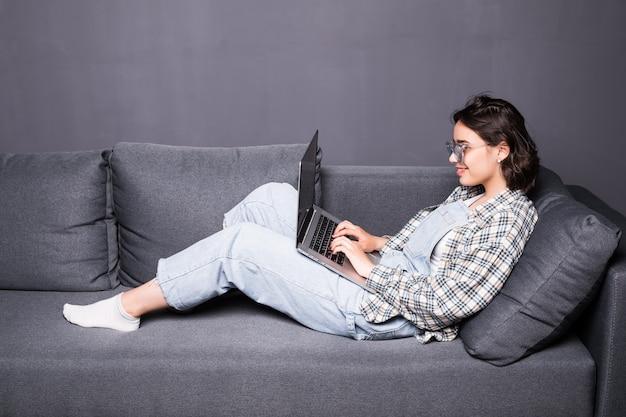 自宅でソファや長椅子に座って彼女のラップトップコンピューターを使用して、笑顔の美しい若いブルネットの女性