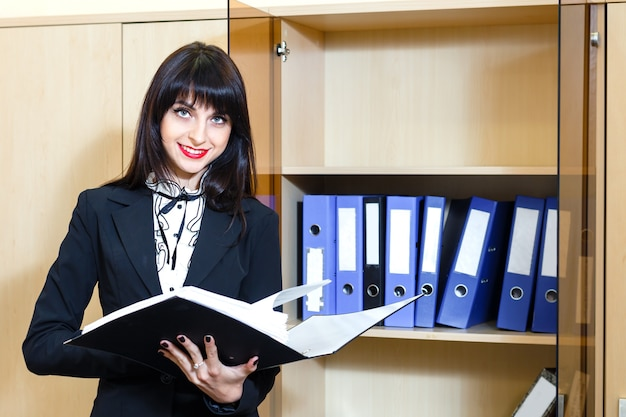 Beautiful young brunette woman holding a folder with documents i
