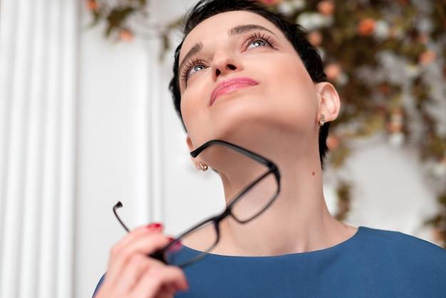 Красивая молодая брюнетка женщина держит в руке очки и смотрит вверх
