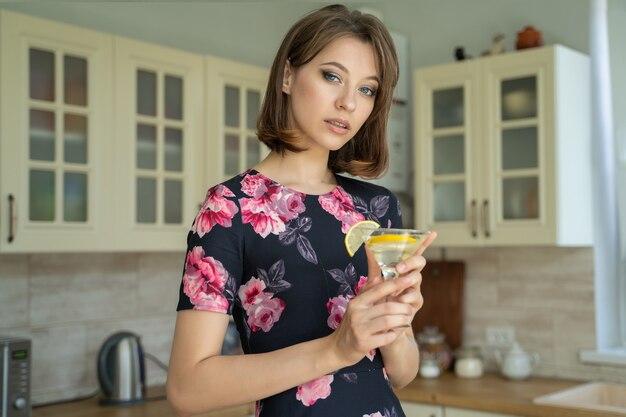 キッチンで一人でドレスを着た美しい若いブルネットの女性は、自宅でレモンとアルコールカクテルを飲みます