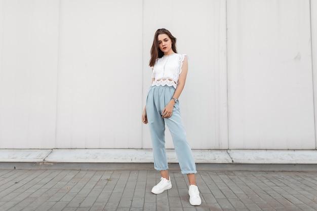 Красивая молодая брюнетка в стильном кружевном топе в винтажных синих брюках в белых кроссовках стоит возле здания в городе.