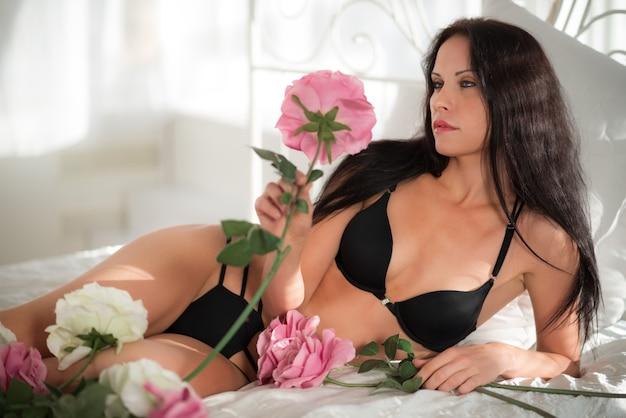 Красивая молодая брюнетка женщина в черном сексуальном нижнем белье, лежа в постели и держа цветок