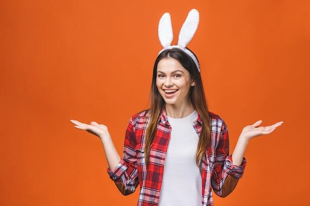 オレンジ色の背景に立っている間カメラを見てバニーの耳の美しい若いブルネットの女性。