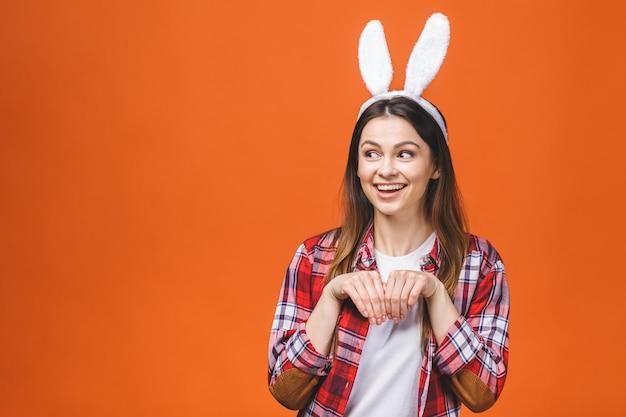 オレンジ色の背景に立っている間バニーの耳の美しい若いブルネットの女性。 Premium写真