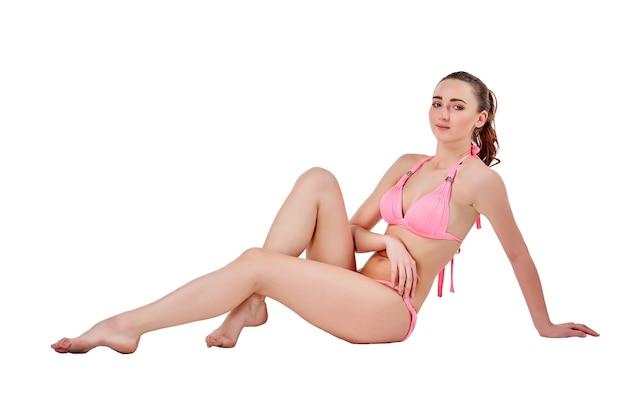 ピンクの水着で座って白い背景で隔離の美しい若いブルネットの女性
