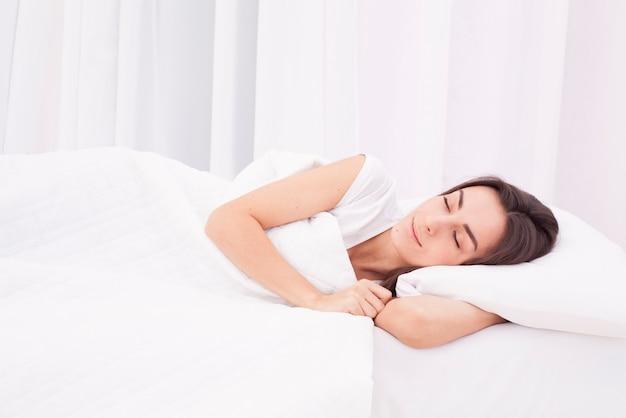 아름 다운 젊은 갈색 머리 여자는 큰 흰색 침대에서 자