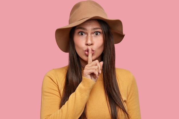 La bella giovane donna castana tiene il dito indice sulle labbra, ha un'espressione sorpresa, chiede silenzio