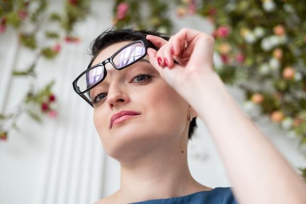 Красивая молодая брюнетка женщина снимает очки с лица рукой и смотрит задумчиво
