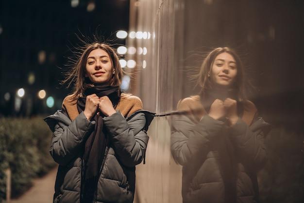 Красивая молодая брюнетка женщина на пространстве ночного города в пуховик