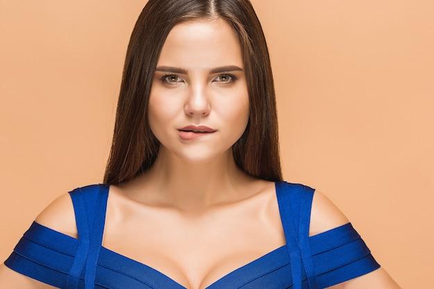 Bella giovane donna castana che posa in un vestito blu
