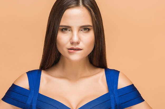 파란 드레스를 입고 포즈를 취하는 아름 다운 젊은 갈색 머리 여자