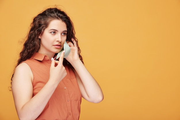 Beautiful young brunette woman putting cloth mask on face on orange, coronavirus concept