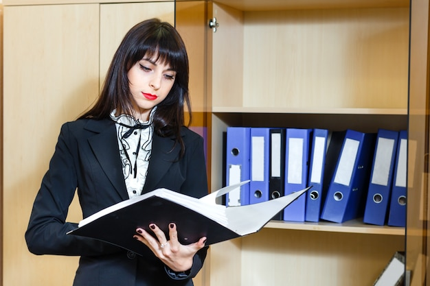 Beautiful young brunette woman reading documents in office.
