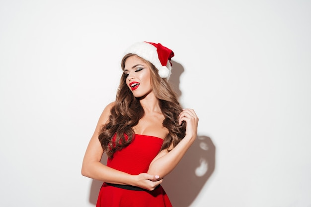 Beautiful young brunette woman in red dress and hat posing isolated over white surface