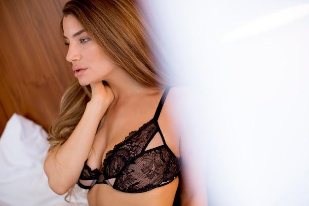 自宅の寝室のベッドの上に座って美しい若いブルネットの女性