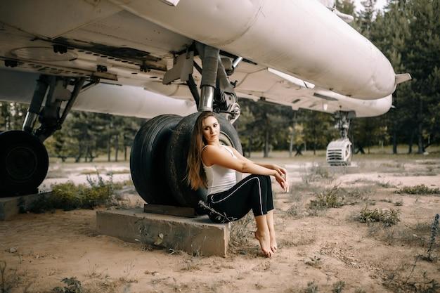 아름 다운 젊은 갈색 머리 여자는 오래 된 군용 항공기의 벽에 서