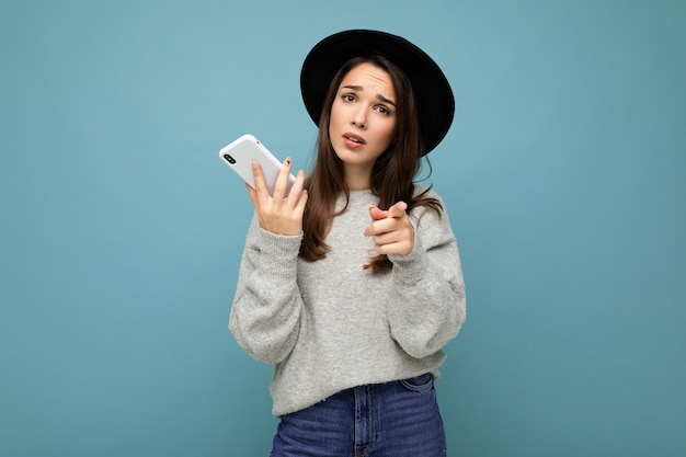 Beautiful young brunette woman thinking pointing finger at you wearing black hat and grey sweater holding smartphone looking to the side texting isolated on background.