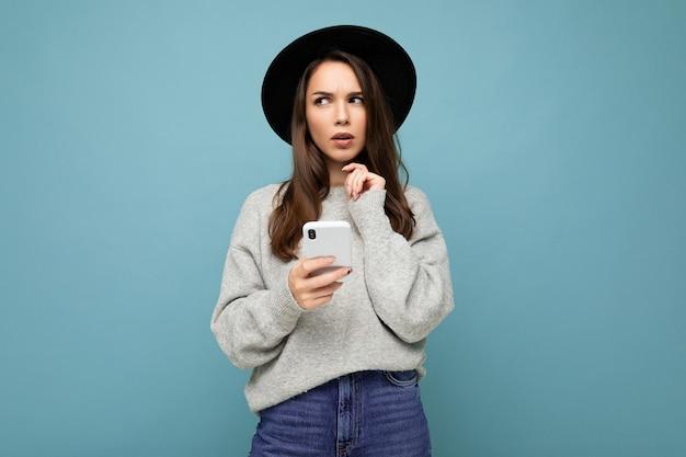 Красивая молодая брюнетка женщина думает в черной шляпе и сером свитере, держа смартфон, глядя в сторону текстовых сообщений, изолированных на фоне.