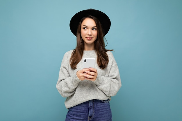 Beautiful young brunette woman thinking wearing black hat and grey sweater holding smartphone looking to the side texting isolated on background.copy space