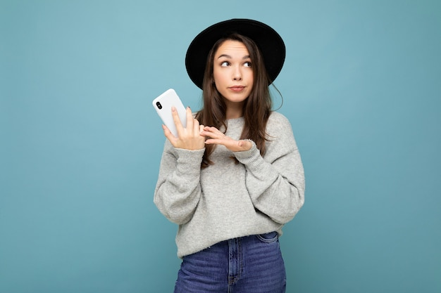 Beautiful young brunette woman thinking wearing black hat and grey sweater holding smartphone looking to the side texting isolated on wall.