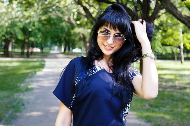 공원에서 골목을 따라 걷는 아름 다운 젊은 갈색 머리 여자